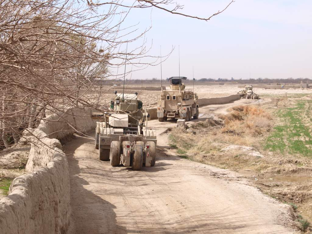 Two husky vehicles are using ground penetrating radars to detect IEDs along a narrow road near Kandahar while a cougar provides security.Photographer : Cpl Sosa 11 march 2011