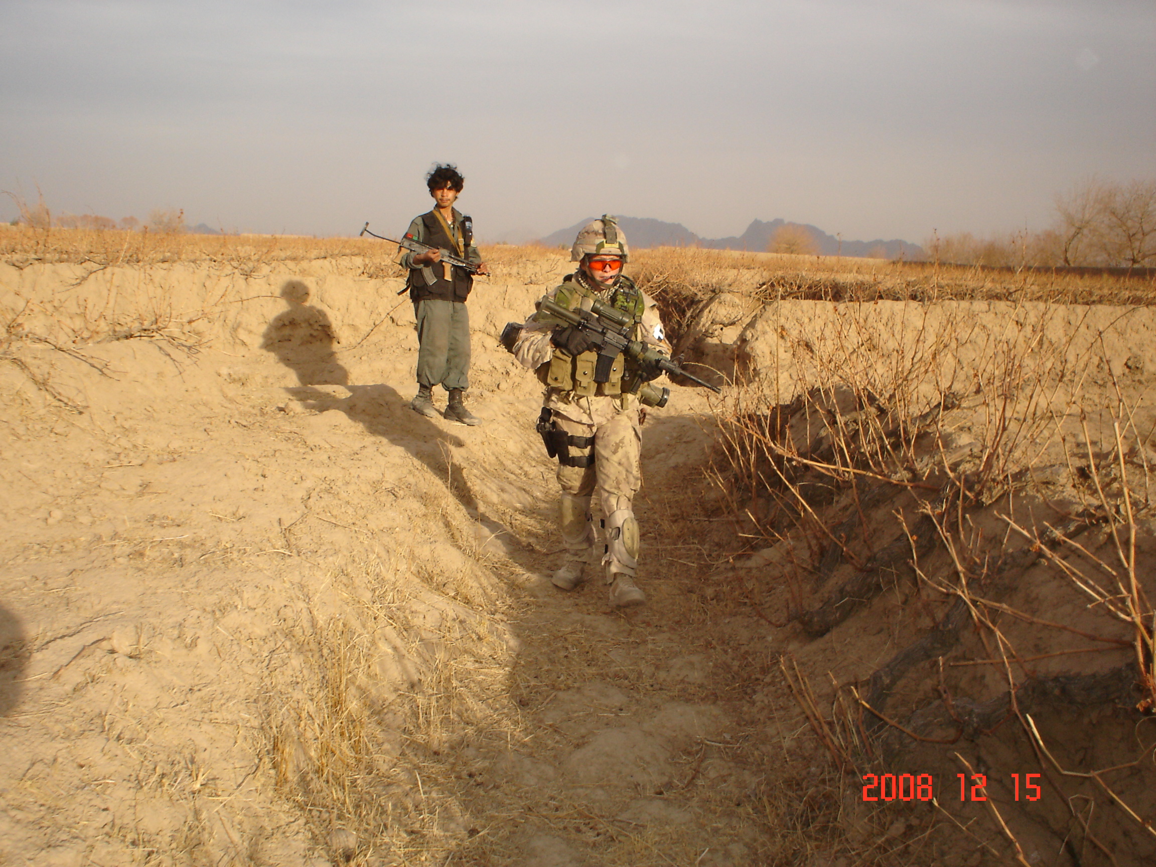 "Taken by our interpreter ""Andy"" Location, Zharey District, Kandahar, Afghanistan December 2008 Marcia Coelho, Corporal Canadian Military Police and members of 1 RCR, part of the Police Operational Mentoring Liaison Team Conducting a foot patrol with members of the Afghanistan Uniformed Police."